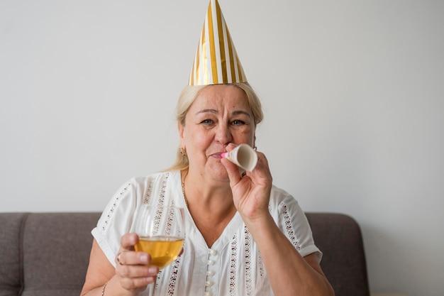 Frau in der quarantäne, die geburtstag mit getränk feiert
