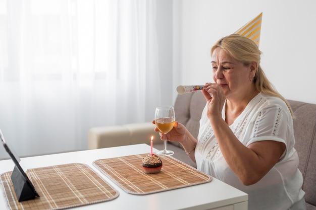 Frau in der quarantäne, die geburtstag mit getränk und laptop feiert