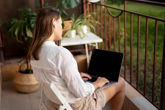 Frau in der quarantäne, die zu hause am laptop arbeitet