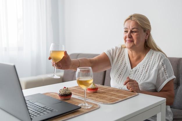 Frau in der quarantäne zu hause, die einen drink mit freunden auf laptop hat