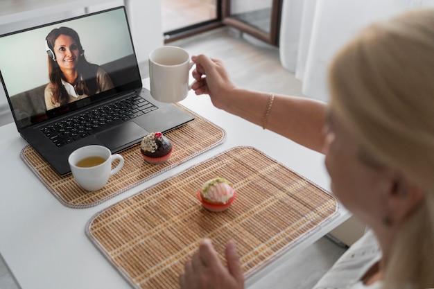 Frau in der quarantäne zu hause, die kaffee mit freunden auf laptop trinkt