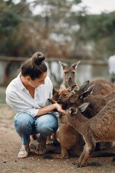 Frau in der reserve spielt mit einem känguru