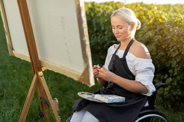 Frau in der rollstuhlmalerei in der natur
