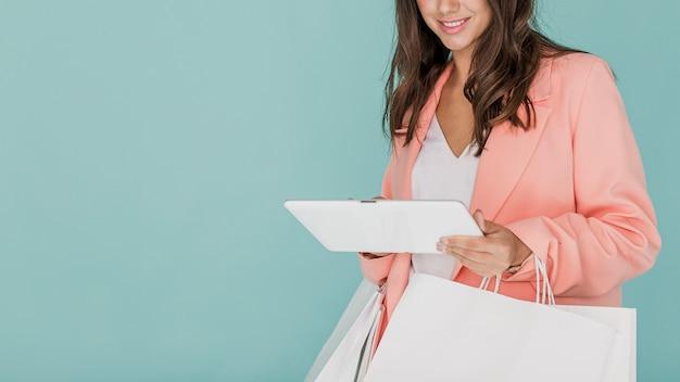 Frau in der rosa jacke mit einkaufstaschen und tablette