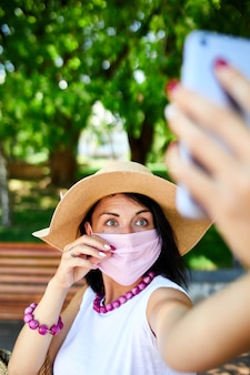 Frau in der rosa medizinischen maske im park nehmen selfie per handy, frau mit atemschutz ist draußen, während sie spricht und video-chat per webcam auf smartphone hat