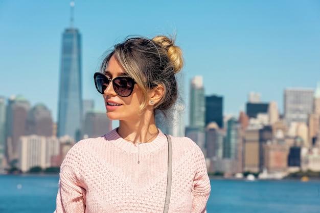 Frau in der rosa strickjacke, die in new york aufwirft