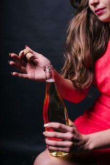 Frau in der rosafarbenen eröffnungschampagnerflasche