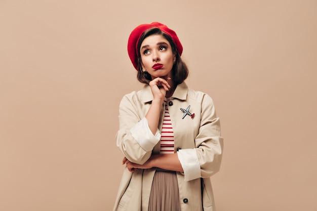 Frau in der roten baskenmütze und im trendigen mantel wirft auf beigem hintergrund auf. trauriges mädchen mit braunen augen und hellen lippen in stilvollen kleidern schaut auf.