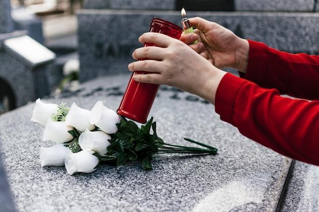 Frau in der roten bluse, die eine kerze anzündet und blumen zu einem geliebten auf dem friedhof setzt.