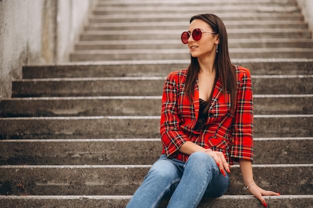 Frau in der roten jacke, die auf der treppe sitzt