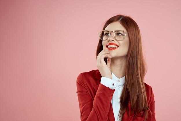 Frau in der roten jacke mit den roten lippen des langen haares der brille