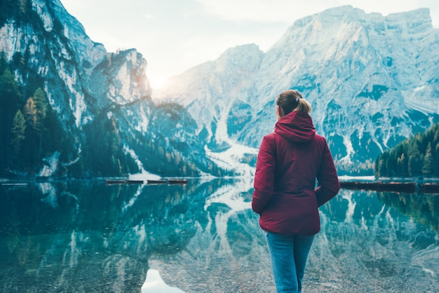 Frau in der roten jacke steht an der küste des braies-sees bei sonnenaufgang im herbst. dolomiten, italien.