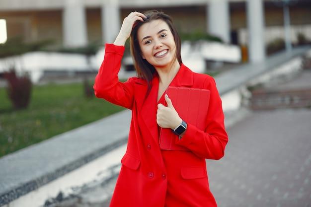 Frau in der roten jacke unter verwendung einer tablette
