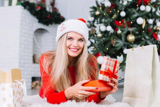 Frau in der roten öffnenden geschenkbox auf boden Kostenlose Fotos