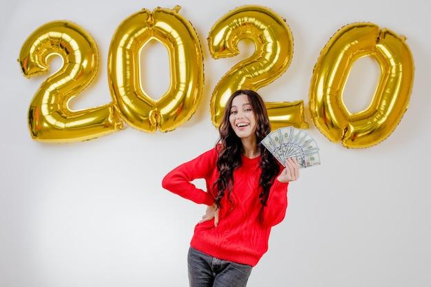 Frau in der roten strickjacke, die hundert dollarscheine vor 2020 ballonen des neuen jahres hält