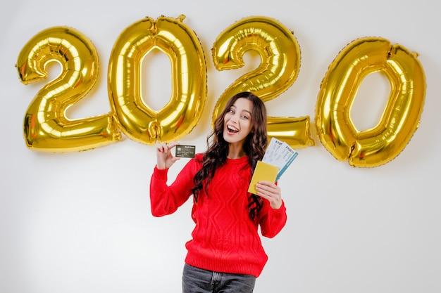 Frau in der roten strickjacke, die schablonenkreditkarte und flugtickets vor 2020 ballonen des neuen jahres hält