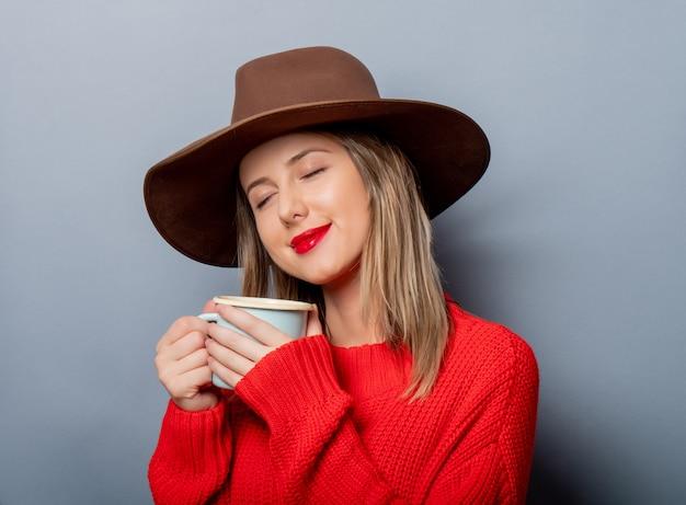 Frau in der roten strickjacke und im hut mit tasse kaffee