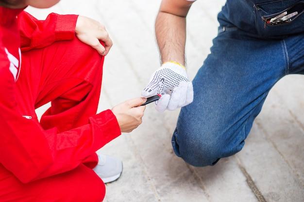 Frau in der roten uniform geben dem mechanischen ingenieur ein instrument herein