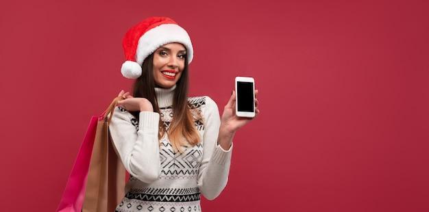 Frau in der roten weihnachtsmütze auf rot