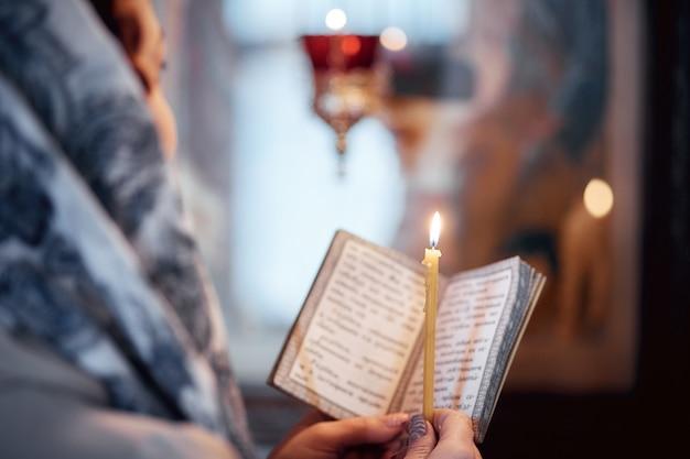 Frau in der russisch-orthodoxen kirche mit roten haaren und einem schal auf dem kopf zündet eine kerze an und betet vor der ikone