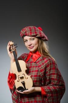 Frau in der schottischen kleidung im musikalischen konzept