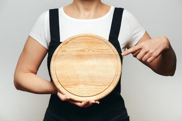 Frau in der schürze, die finger auf rundes hölzernes pizza-schneidebrett zeigt.