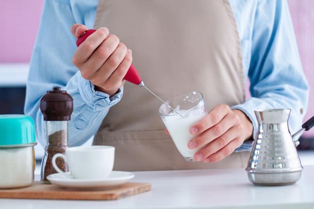 Frau in der schürze, die kaffee mit einem milchschäumer an der küche zu hause macht