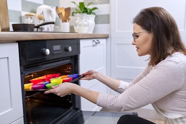 Frau in der schürze, die zu hause cupcakes zubereitet. hausfrau, die backen mit gebackenen muffins aus dem ofen herauszieht, hausgemachtes gesundes essen, hobby