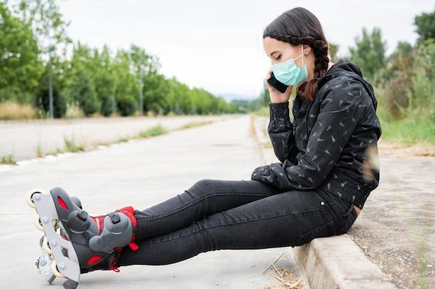 Frau in der schützenden gesichtsmaske auf rollschuhpause, die auf der straße sitzt und handy während des ausbruchs der coronavirus-pandemie benutzt. urban girl spricht am telefon und trägt rollschuhe.