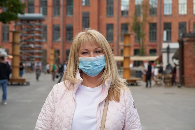 Frau in der schützenden medizinischen gesichtsmaske, die draußen im öffentlichen platz steht