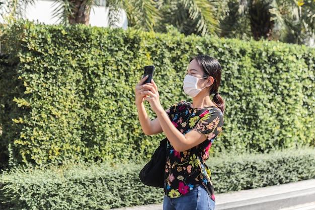 Frau in der schutzmaske, die foto mit ihrem handy macht.