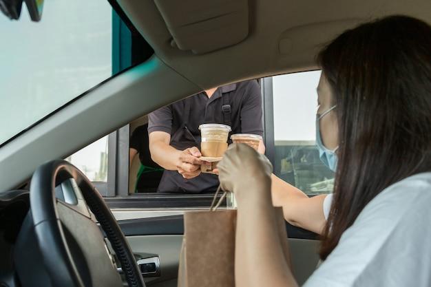Frau in der schutzmaske, die kaffee während des ausbruchs des coronavirus beim durchfahren nimmt