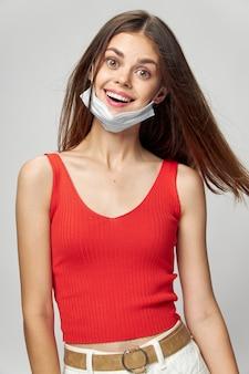 Frau in der schutzmaske gegen coronavirus, der im studio aufwirft.
