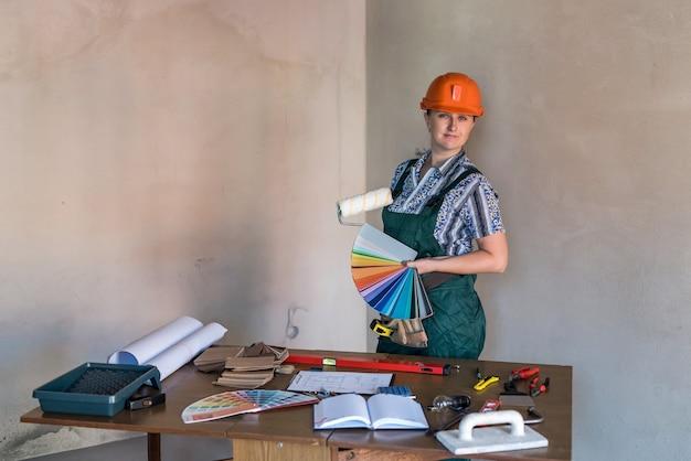 Frau in der schutzuniform, die malwerkzeuge zeigt