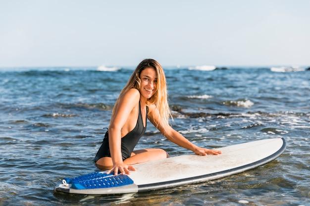 Frau in der schwarzen badebekleidung nahe surfbrett