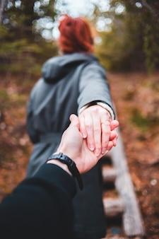 Frau in der schwarzen jacke, die ihre hand hält