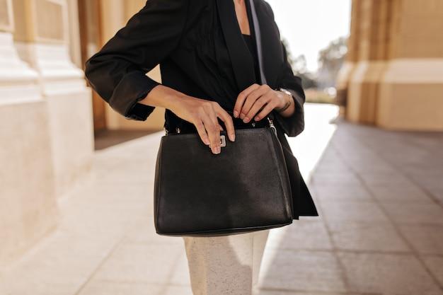 Frau in der schwarzen jacke und in der weißen hose, die draußen dunkle handtasche halten. frau in der modernen kleidung, die mit stilvoller tasche im freien aufwirft.