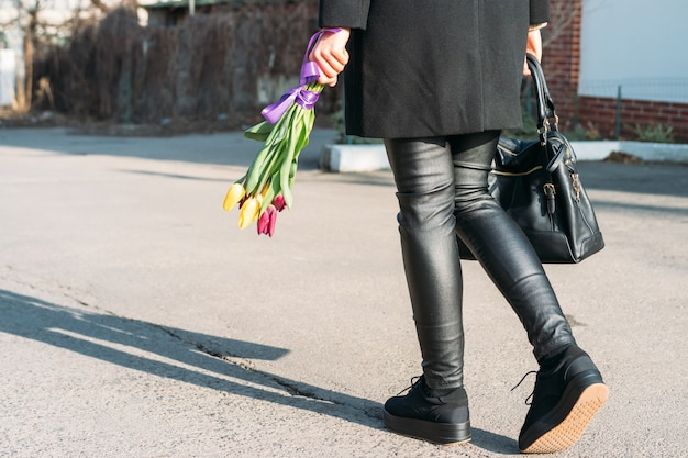 Frau in der schwarzen kleidung gehend hinunter die straße mit einem hellen blumenstrauß