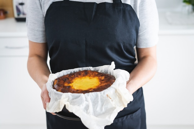 Frau in der schwarzen schürze, die einen käsekuchen zeigt. küchenkonzept.
