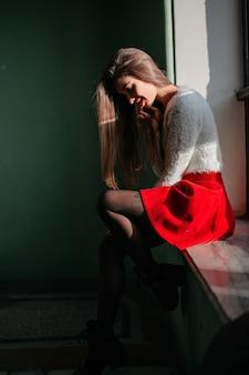 Frau in der schwarzen strumpfhose, die auf fensterbank sitzt