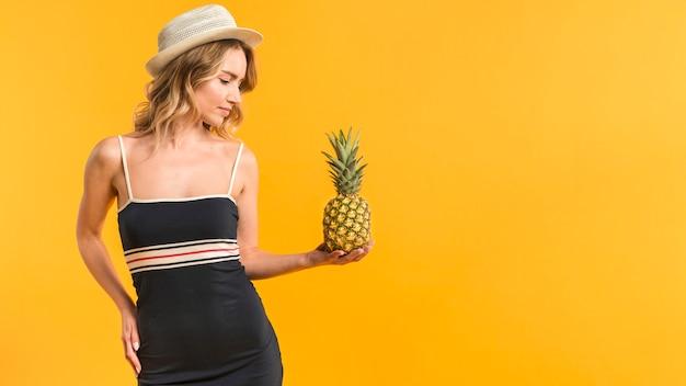 Frau in der sommerkleidung, die ananas betrachtet