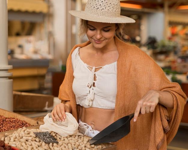 Frau in der sommerkleidung, die trockenfutter am marktplatz nimmt