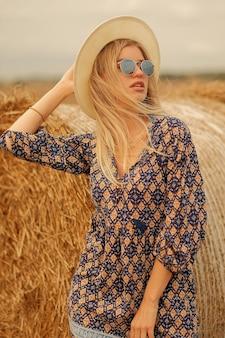 Frau in der sonnenbrille, die hut und kleid in sommerwiese nahe heuhaufen trägt