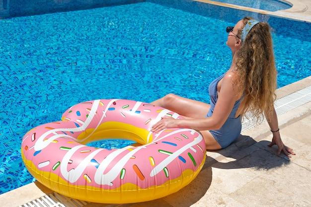Frau in der sonnenbrille, die mit aufblasbarem donut nahe schwimmbad am resort aufwirft