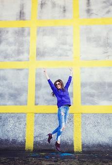 Frau in der sonnenbrille, die oben springt