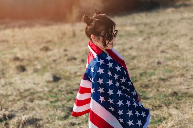 Frau in der sonnenbrille eingewickelt in der amerikanischen flagge