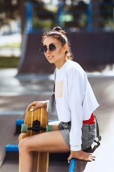 Frau in der sonnenbrille wirft mit einem skateboard in ihren händen an einem warmen sonnigen morgen im park auf