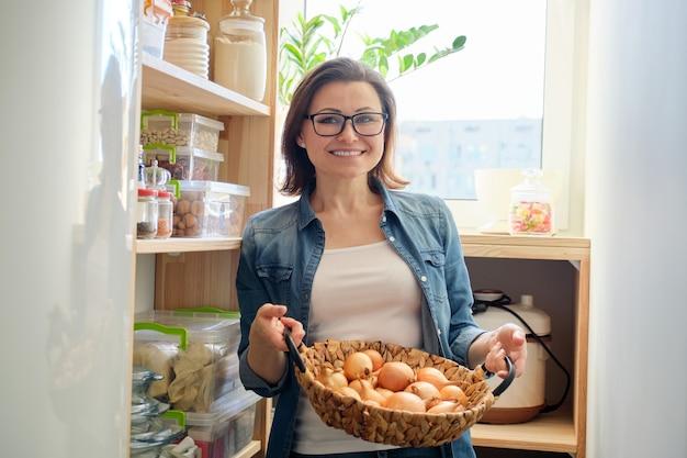 Frau in der speisekammer, die korb mit zwiebeln nimmt