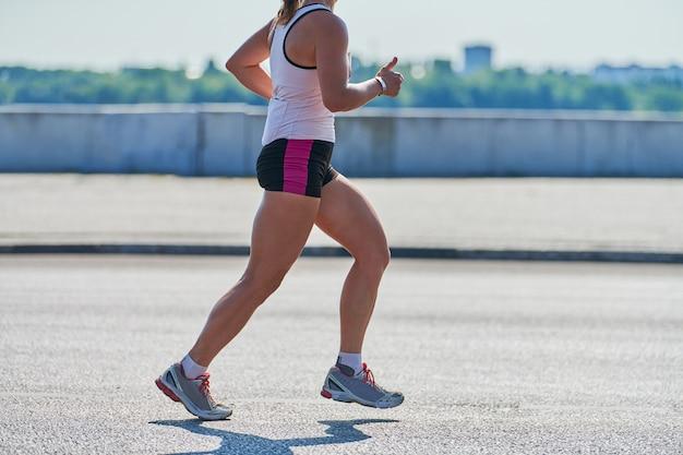 Frau in der sportbekleidung, die auf der straße läuft