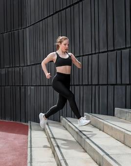 Frau in der sportbekleidung, die draußen läuft